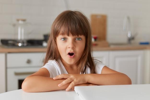 Mała dziewczynka siedzi przy stole z zamkniętym laptopem w domu. śliczna dziewczyna patrząca na kamerę z otwartymi ustami, będąc w szoku, ciemnowłose dziecko płci żeńskiej jest zdumione po zobaczeniu zaskoczonych treści.