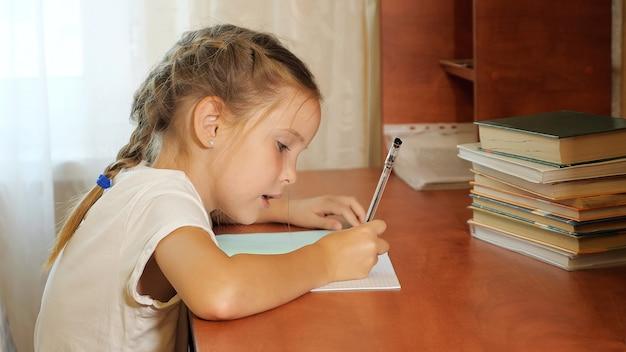 Mała Dziewczynka Siedzi Przy Stole Ze Stosem Książek I Odrabia Pracę Domową, Opierając Się Na Dłoni Premium Zdjęcia