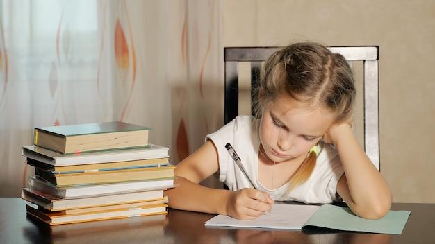 Mała dziewczynka siedzi przy stole ze stosem książek i odrabia pracę domową, opierając się na dłoni