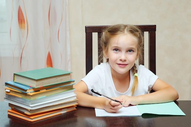 Mała dziewczynka siedzi przy stole ze stosem książek, odrabia pracę domową i patrzy na kamerę