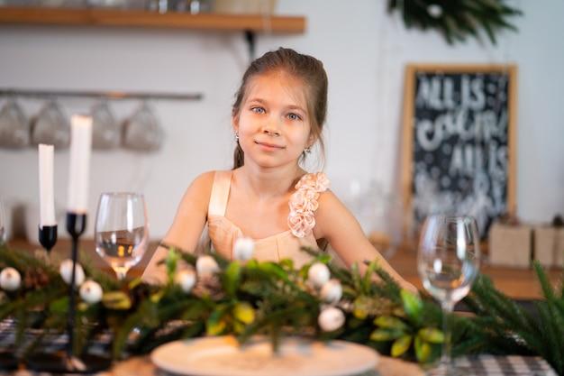 Mała dziewczynka siedzi przy świątecznym stole w noc bożego narodzenia