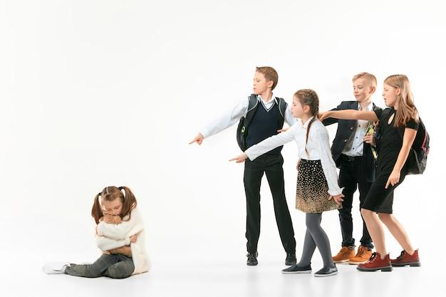 Mała dziewczynka siedzi samotnie na podłodze i cierpi z powodu zastraszania, podczas gdy dzieci szydzą. smutna młoda uczennica siedzi na białej ścianie.