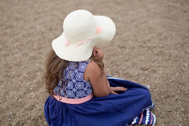 Mała dziewczynka siedzi, trzymając letni kapelusz i piękną niebieską sukienkę na plaży