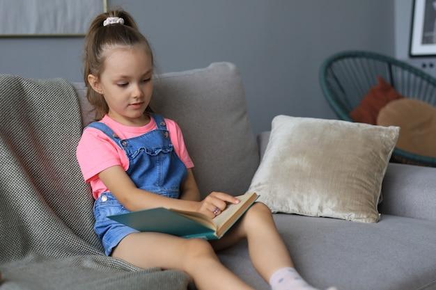 Mała dziewczynka siedzi w domu i odrabia lekcje, samodzielne studiowanie materiału, czytanie książki. pojęcie kształcenia na odległość.