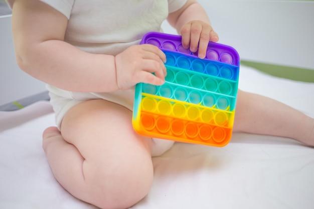Mała dziewczynka siedzi w domu na łóżku i bawi się nową antystresową zabawką pop-it, popularną wśród dzieci. pomysł na rozwój dziecka.