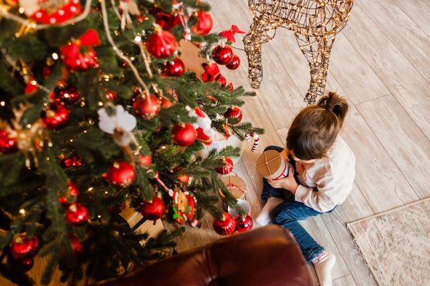 Mała dziewczynka siedzi w domu przy choince z prezentami. widok z góry. nowy rok 2022.