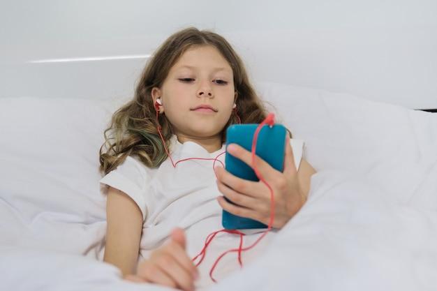 Mała dziewczynka siedzi w domu w łóżku, z smartphone i hełmofonami