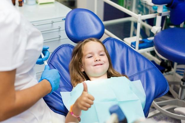 Mała dziewczynka siedzi w fotelu u dentysty.
