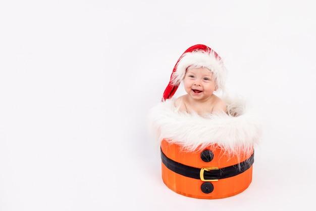 Mała dziewczynka siedzi w kapeluszu santa w koszu na białym tle