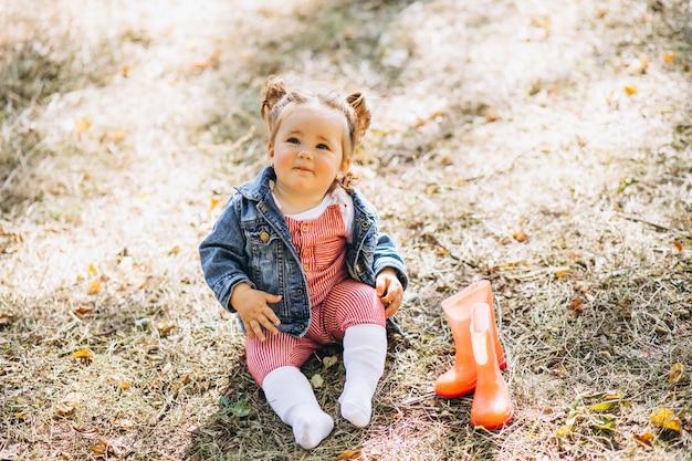 Mała dziewczynka siedzi w parku z podeszczowymi butami