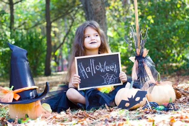 Mała dziewczynka siedzi w parku z żółtymi liśćmi w stroju wiedźmy. miotła, dynia, maska nietoperza, kapelusz czarownicy. halloween.