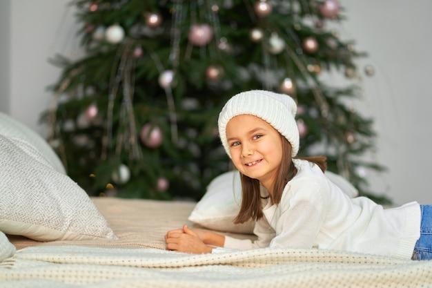 Mała dziewczynka siedzi w pobliżu choinki