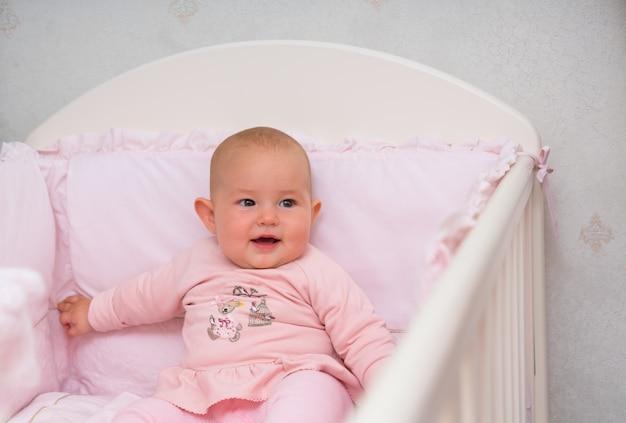 Mała dziewczynka siedzi w różowym łóżeczku na sobie ładny pasujący różowy strój uśmiecha się do kamery