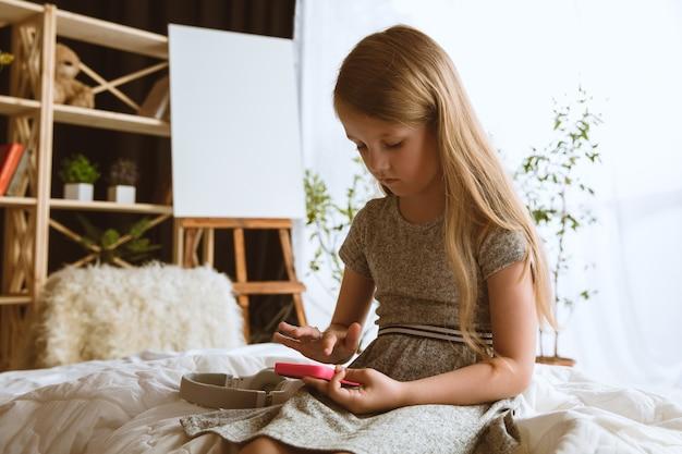 Mała dziewczynka siedzi w swoim pokoju ze smartfonem i grami