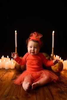 Mała dziewczynka siedzi z dyniami jacka i świecami na czarnej ścianie. dziecko patrzy w ramkę ze zmrużonymi oczami.
