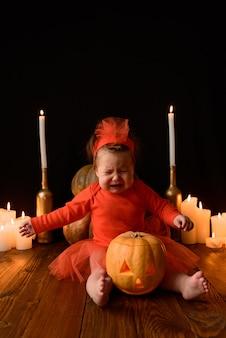 Mała dziewczynka siedzi z dyniami jacka i świecami na czarnej ścianie. dziewczyna płacze ze strachu.