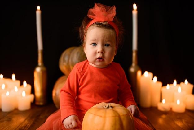 Mała dziewczynka siedzi z dyniami jacka i świecami na czarnej ścianie. zbliżenie.
