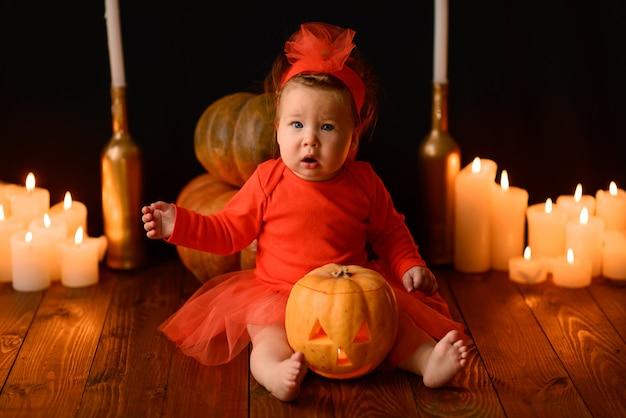 Mała dziewczynka siedzi z dyniami jacka i świecami na czarnej ścianie