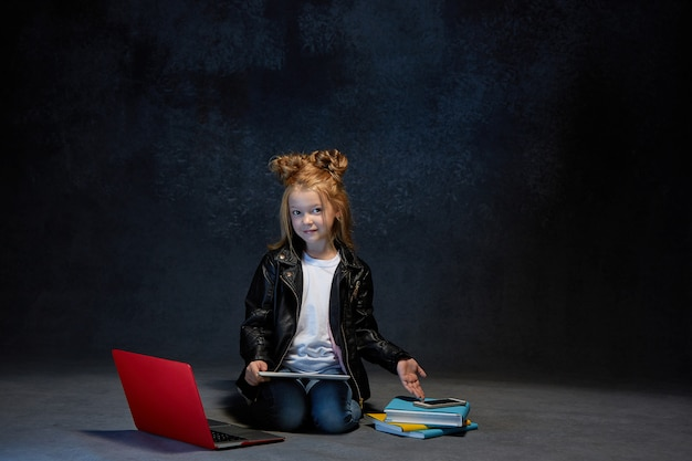 Mała dziewczynka siedzi z gadżetami