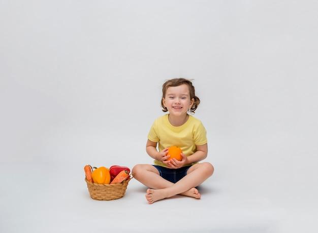 Mała dziewczynka siedzi z koszem warzyw i owoców na białej przestrzeni. śliczna dziewczyna z ogonami uśmiecha się i trzyma w rękach pomarańczę. wolna przestrzeń.