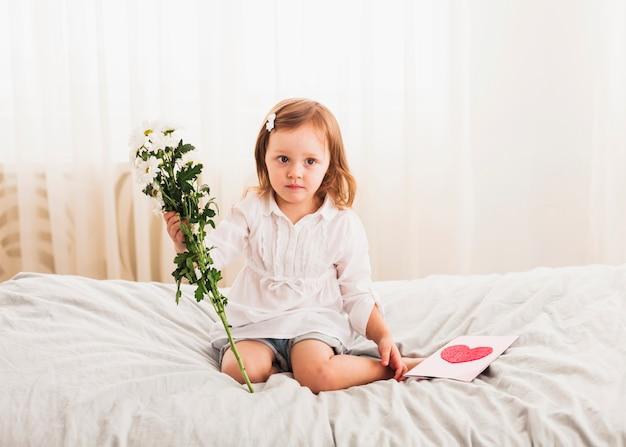 Mała dziewczynka siedzi z kwiatami i kartkę z życzeniami