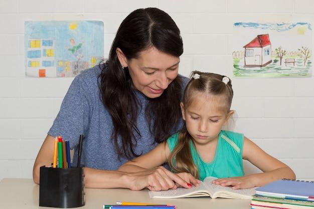 Mała dziewczynka siedzi z mamą przy stole i uczy się czytać podręcznik