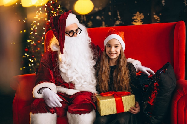 Mała dziewczynka siedzi z santa i prezenty na boże narodzenie
