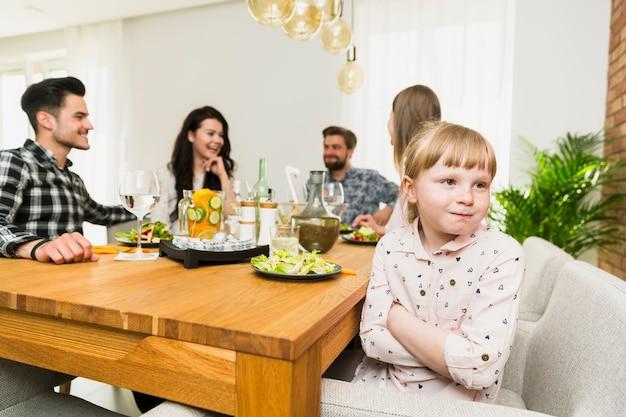 Mała dziewczynka siedzi z śmieszne dorosłych przy stole