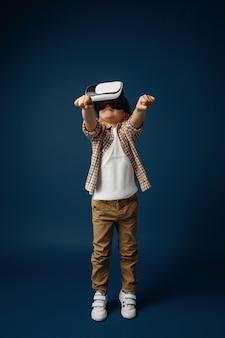 Mała dziewczynka skacze z okularami zestaw słuchawkowy wirtualnej rzeczywistości na białym tle