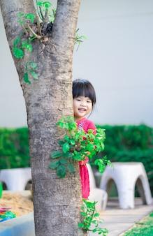 Mała dziewczynka skrada się za drzewem w parku