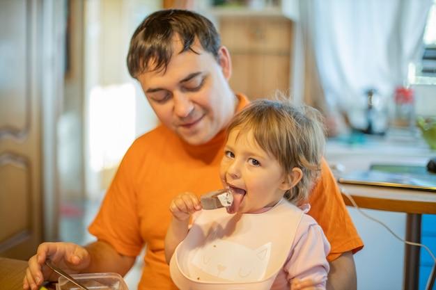 Mała dziewczynka słodkie maluch jedzenie lody popsicle siedzi na kolanach taty, nieostrość.