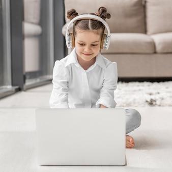Mała dziewczynka słucha jej nauczyciel przez hełmofonów w domu