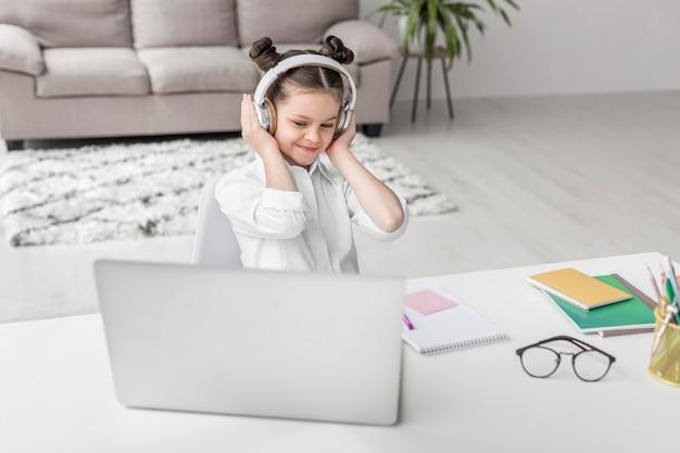 Mała dziewczynka słucha jej nauczyciel przez hełmofonów