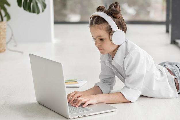 Mała dziewczynka słucha jej nauczyciel z hełmofonami