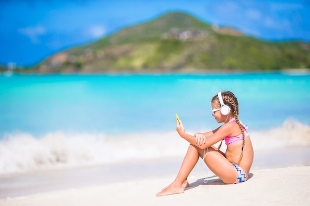 Mała dziewczynka słucha muzyka na hełmofonach na karaibskiej plaży