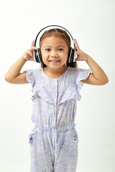 Mała dziewczynka słucha muzyka na hełmofonach