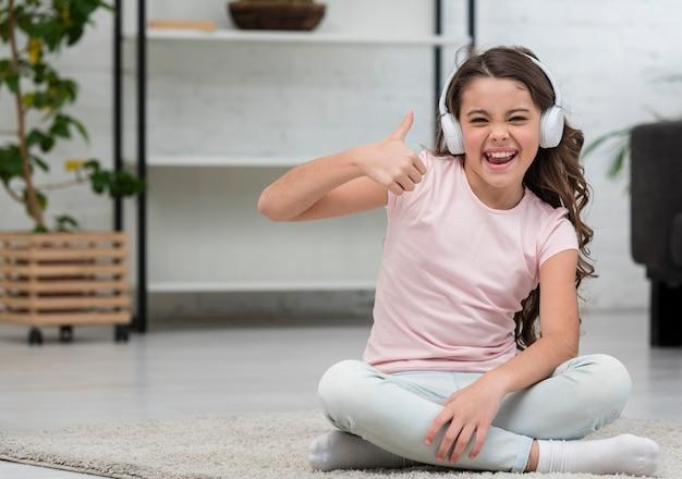 Mała dziewczynka słucha muzykę przez hełmofonów