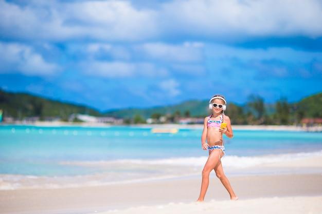 Mała dziewczynka słucha muzyki przez słuchawki i chodzi na plaży