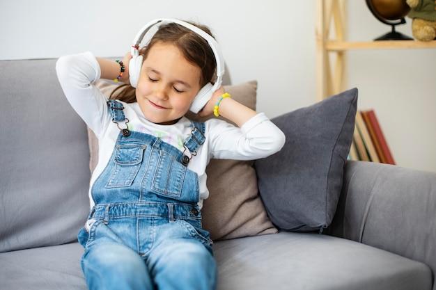 Mała dziewczynka słucha muzyki przez słuchawki