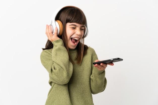 Mała dziewczynka słucha muzyki z telefonem komórkowym na białym tle słuchania muzyki