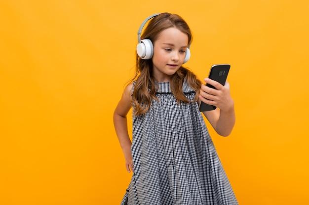 Mała dziewczynka słucha swojej ulubionej muzyki w słuchawkach na pomarańczowym tle.