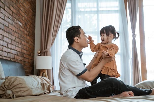 Mała dziewczynka śmiała się radośnie, trzymając nos ojca