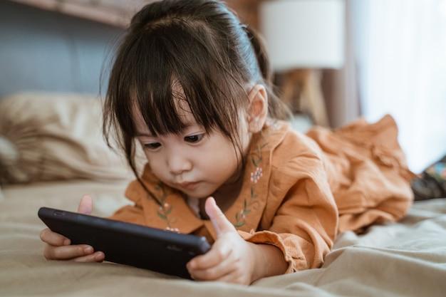 Mała dziewczynka śmiała się radośnie, trzymając telefon