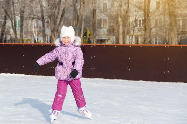 Mała dziewczynka śmieje się i jeździ na łyżwach po lodzie.