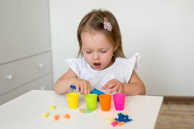 Mała dziewczynka sortuje figurki zwierząt według koloru i wrzuca je do odpowiedniego kubka.