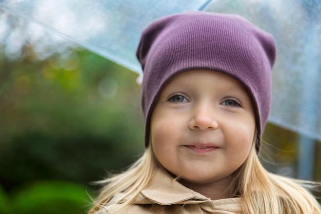 Mała dziewczynka spaceru w parku pod parasolem podczas deszczu