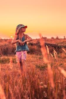 Mała dziewczynka spaceruje po polu podczas wakacji o zachodzie słońca i odpoczywa w wiosce