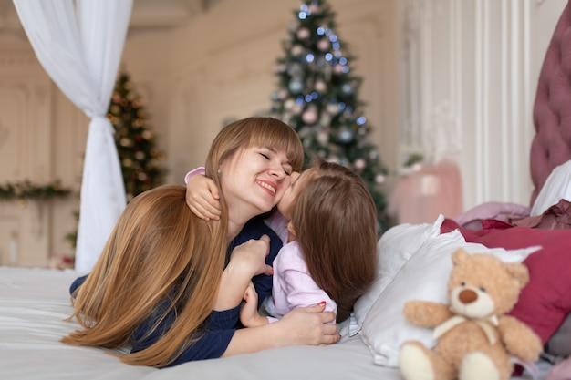 Mała dziewczynka spędza czas bawiąc się z mamą leżąc w łóżku. opowieść świąteczna. szczęśliwe dzieciństwo.