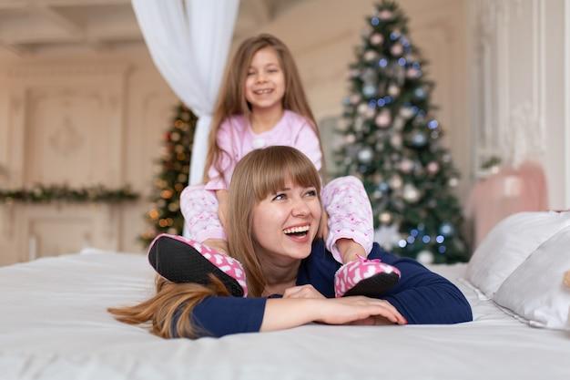 Mała dziewczynka spędza czas na zabawie z mamą leżąc w łóżku. świąteczna opowieść. szczęśliwe dzieciństwo.