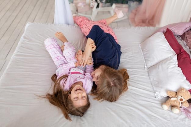 Mała dziewczynka spędza czas na zabawie z mamą leżąc w łóżku